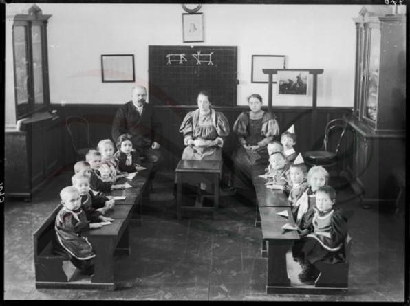 Oktatás. Padokban ülő kisgyerekek két nevelőnővel és egy férfival. A gyerekek intézeti egyenruhában láthatók.